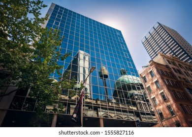 Sydney, NSW, Australia - October 21, 2019: Reflections in a glass wall of some of the most iconic landmarks in Sydney CBD including Queen Victoria Building and the City Tower Eye in Sydney, Australia.