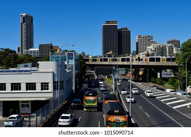 SYDNEY, NSW, AUSTRALIA - OCTOBER 30: Traffic on Eastern Distributor and public railway crossing bridge, with buildings and skyscrapers, on October 30, 2017 in Sydney, Australia