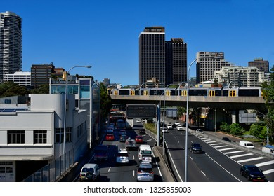SYDNEY, NSW, AUSTRALIA - OCTOBER 30, 2017:Traffic on Eastern Distributor and public railway crossing bridge, with buildings, skyscraper and Horizon apartments