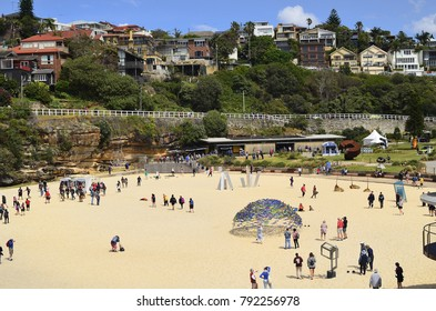 SYDNEY, NSW, AUSTRALIA - OCTOBER 31: Unidentified people on Tamarama beach, homes and different artworks from outdoor exhibition Sculpture-by-the-Sea, on October 31, 2017 in Sydney, Australia