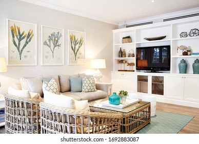 Sydney, NSW/Australia-July 15 2018:Interior photography of a Hampton's style lounge room with cane furniture, framed botanical art and Moroccan print aqua rug