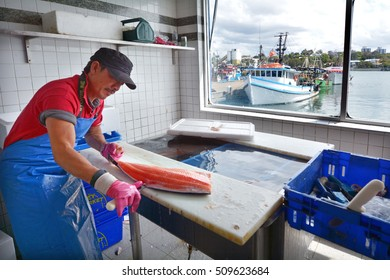 SYDNEY - OCT 20 2016: Fisherman cleans a Salmon fish in Sydney Fish Market, a Large marketplace  and a major tourist attraction featuring shops for seafood, deli items and restaurants.