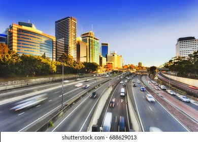 Sydney Warringah freeway going through high-rise buildings of North Sydney. Tall modern architectural office towers and serviced apartments face rising sun above multi-lane transport corridor.