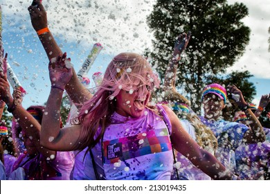 SYDNEY,AUSTRALIA - AUGUST 24,2014: Competitors in the 'Color Run' fun run in Centennial Park. Runners are doused in coloured powder, bubbles and water as they run the 5K course.