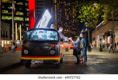 SYDNEY,AUSTRALIA - JUNE 23,2017: A couple buy a German sausage meal from food vendors operating out of a VW Kombi van. Circular Quay is Sydney's main transport hub.