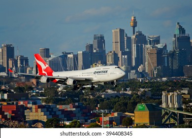 SYDNEY,AUSTRALIA - MARCH 19,2016: A QANTAS Boeing 747 flies extremely low past buildings and industrial sites on its final approach to the city's airport.