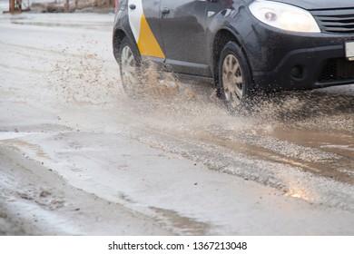 Syktyvkar,Komi /Russia,April 10,2019/Moving car sprays puddle when heavy rain drops on concrete.