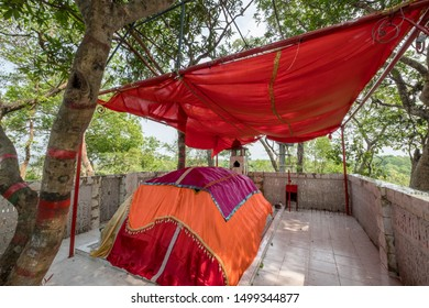 SYLHET, BANGLADESH - 12 APRIL, 2018: Colorful fabrics cover the tomb of a Muslim saint at a shrine or mazar under a red canopy.