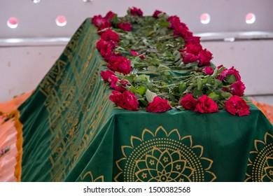 SYLHET, BANGLADESH - 14 APRIL, 2018: Roses cover the tomb of a Muslim saint at a shrine or mazar.