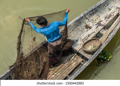 SYLHET, BANGLADESH - 14 APRIL, 2018: A fisherman raises a fishing net in preparation for cleaning it on a boat on a river.