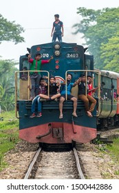 SYLHET, BANGLADESH - 14 APRIL, 2018: Young men sit on and one stands atop the diesel locomotive of a train travelling in rural Bangladesh.