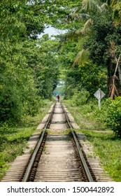 SYLHET, BANGLADESH - 14 APRIL, 2018: A man, distorted by heat haze, carries an empty basket along railway tracks through rainforest.