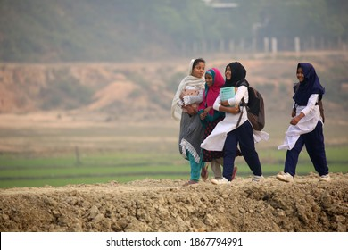 Sylhet, Bangladesh - 27 January 2020: The students are going to school by crossing the village path.
