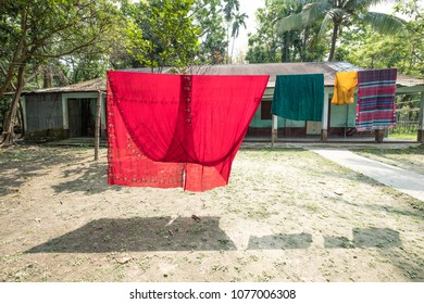 SYLHET, BANGLADESH - 9 APRIL, 2018: Colorful clothing including a sari hangs to dry on a line in the garden of a house with a tin roof and veranda.