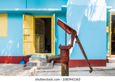 SYLHET, BANGLADESH - 9 APRIL, 2018: A hand-operated water pump stands in the concrete courtyard of a Bangladeshi house painted yellow, red and blue with the entrance to the kitchen in the background.