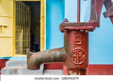 SYLHET, BANGLADESH - 9 APRIL, 2018: Close-up of hand-operated water pump standing in the concrete courtyard of a Bangladeshi house painted yellow, red and blue with the entrance to the kitchen behind.