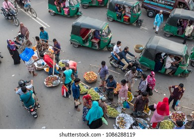 SYLHET, BANGLADESH - 9 APRIL, 2018: Seen from above, pedestrians buy fruit from market sellers on a street busy with rickshaw and motorcycle traffic.