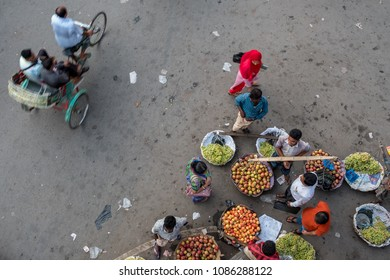 SYLHET, BANGLADESH - 9 APRIL, 2018: Seen from above, pedestrians buy fruit from market sellers while a cycle rickshaw passes with passengers.