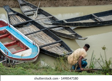 SYLHET, BANGLADESH - APRIL 10, 2018: A boatman in a loincloth prepares to board one of a number of boats on a muddy canal in a rural area.