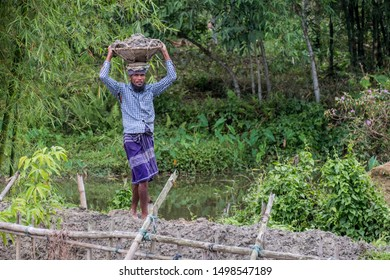 SYLHET, BANGLADESH - APRIL 10, 2018: A farmer in a loincloth carries a basketful of mud on his head as he builds a dam to catch fish.