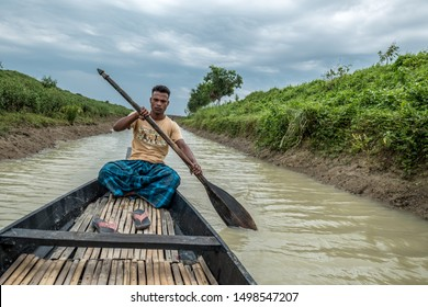 SYLHET, BANGLADESH - APRIL 10, 2018: A boatman in a loincloth paddles along a muddy canal in a rural area.