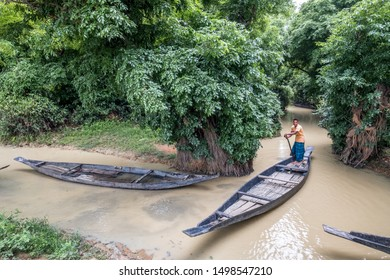 SYLHET, BANGLADESH - APRIL 10, 2018: A boatman in a loincloth steers one of a number of boats on a muddy waterway in a rural area.