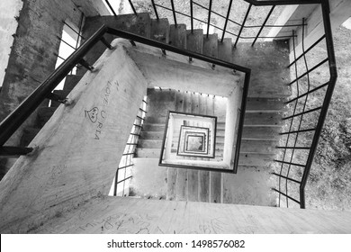 SYLHET, BANGLADESH - APRIL 10, 2018: Looking down the staircase of a square tower in a park in rural Bangladesh with grafitti on the walls.