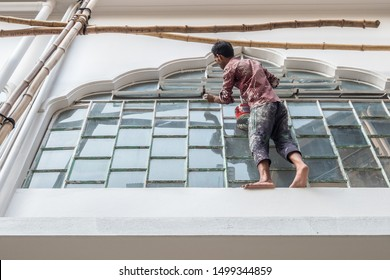 SYLHET, BANGLADESH - APRIL 11, 2018: A laborer paints windowframes while standing precariously on a windowledge with no safety gear.