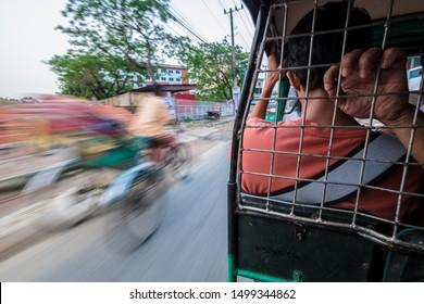 SYLHET, BANGLADESH - APRIL 11, 2018: A motorised rickshaw speeds past a cycle rickshaw on a street in urban Bangladesh.