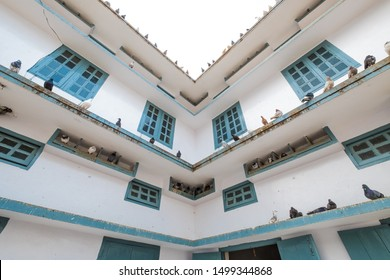 SYLHET, BANGLADESH - APRIL 11, 2018: Pigeons rest on ledges and in boxes at the famous Hazrat Shahjalal Mazar Sharif Islamic shrine where they are venerated.