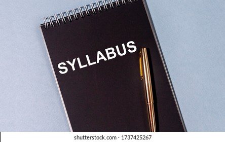 Syllabus word text on black notebook with golden pen on blue table. Education concept.