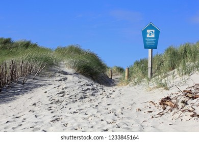 Sylt, Germany - June, 2018: Path through the dunes and sign: Schleswig-Holstein Wadden Sea National Park. The coast of Sylt is changing by storm, waves and erosion. The dunes are stringent protect.