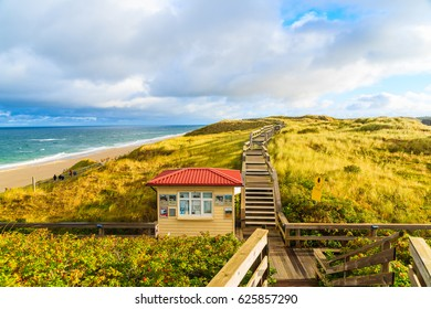 SYLT ISLAND, GERMANY - SEP 11, 2016: Coastal walkway along Wenningstedt beach at sunrise, Sylt island, North Sea, Germany.