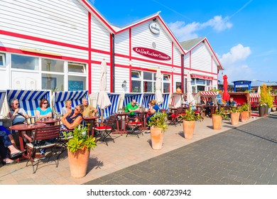SYLT ISLAND, GERMANY - SEP 6, 2016: people dining in restaurant beach chairs in List port on northern coast of Sylt island, Germany.