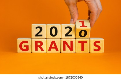 Symbol of 2021 New Year. Male hand flips wooden cubes and changes the inscription 'Grants 2020' to 'Grants 2021'. Beautiful orange background, copy space. Business and 2021 new year grants concept.