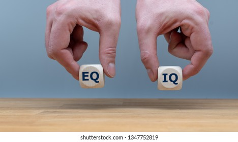 "Symbol of the balance between emotional intelligence and the intelligence quotient.  Hands are holding two dice with the letters ""EQ"" and ""IQ"" in front of a grey background."