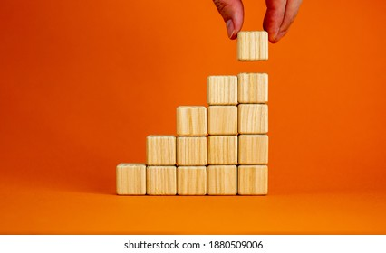 Symbol of building success foundation. Men hand put wooden cube on the pyramid from wooden blocks. Beautiful orange background, copy space. Business and building success foundation concept.