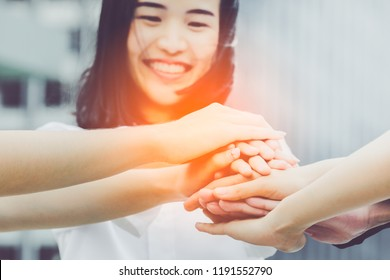 Symbol of Cheerful Smiling Responsible Collaboration Business Teamwork. Group of smart young multiethnic students hands on top of each other as symbol of their Trustworthy partnership.