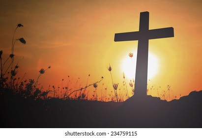 Symbol of christian and catholic: Silhouette cross on autumn sunrise background