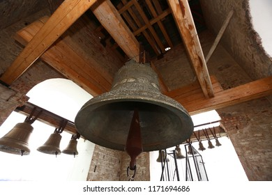 a symbol of the Christian faith, an old church bell tower, a bell ringing on a religious holiday, a bell ringer strikes a large old iron bell, making melodic sounds