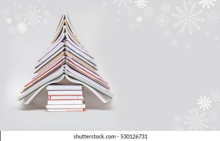 symbol Christmas tree from a colorful books on grey background. Empty copy space for your greetings