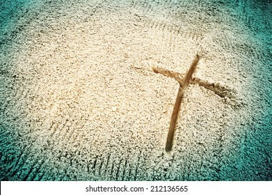 Symbol of the cross drawn in the sand