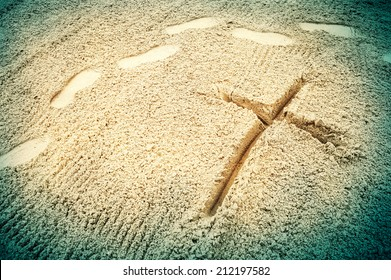 Symbol of the cross drawn in the sand with human footprints passing by