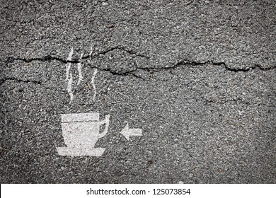 Symbol of a cup of steaming hot coffee with an arrow painted on the surface of a cracking asphalt road for the concept of highway rest stop cafe.