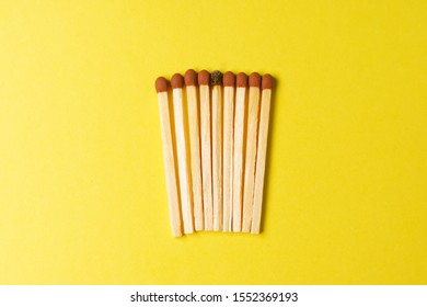 Symbol of danger with matches on yellow  background top view , pile of match arrange in a row with one  Burnt match , unlit matches , unique and various concept