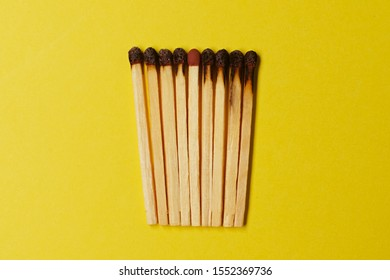 Symbol of danger with matches on yellow  background top view , pile of match arrange in a row with one  unBurnt match , unlit matches , unique and various concept