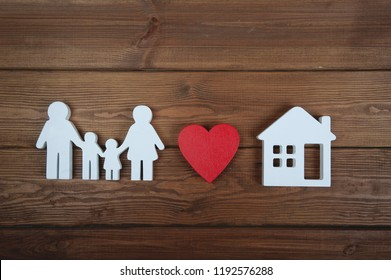 Symbol of family, house and heart on wooden background. Home insurance. Property insurance and security. Health care and insurance concept. Life insurance for whole family.