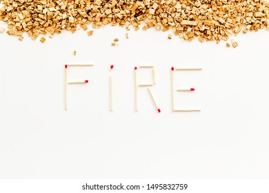Symbol of fire in woods with fire word from matches and kindling frame on white background top view