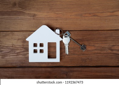 Symbol of house with key on wooden background. Home insurance. Property insurance and security.