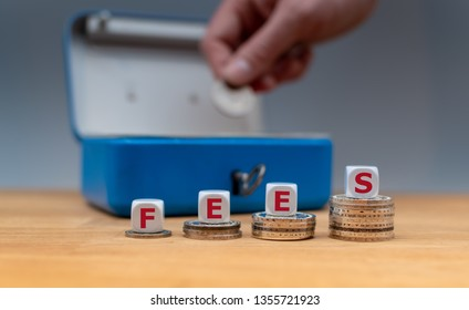 "Symbol for increasing fees. Dice placed on stacks of coins form the word ""fees""."